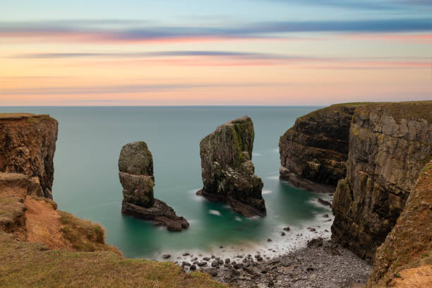 Majestic landscape image of Elegug Stacks in Wales long exposure during stunning colorful sunset stock photo