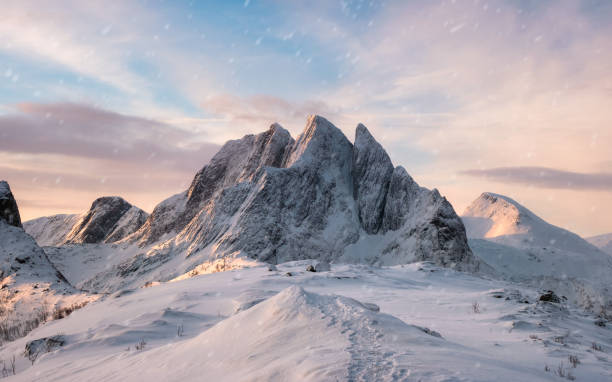 Majestic mountain range with snowfall at sunrise morning Panorama Majestic mountain range with snowfall at sunrise morning on Segla island, Senja, Norway mountains in mist stock pictures, royalty-free photos & images