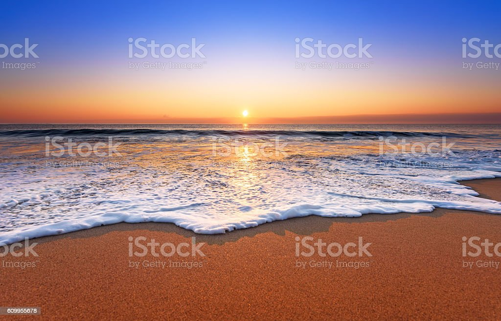Majestic ocean sunset with a breaking wave. stock photo