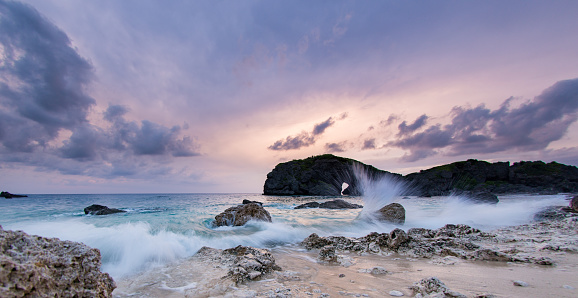 A majestic rocky seascape at dusk in Okinawa with purple pink sky and a long exposure has rendered the water soft and blurry.