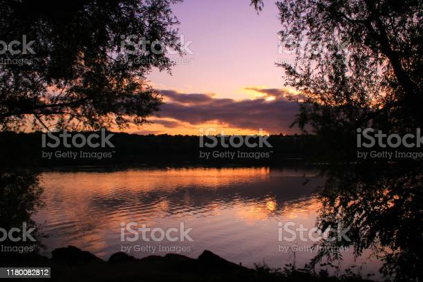 Photo of Majestic sunset over a lake. Horizon line in the background. Cumulonimbus clouds that is reflected.