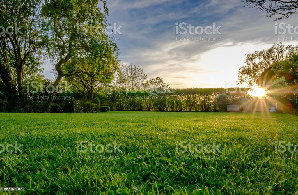 Majestic sunset seen in late spring, showing a recently cut and well maintained large lawn in a rural location. royalty-free stock photo