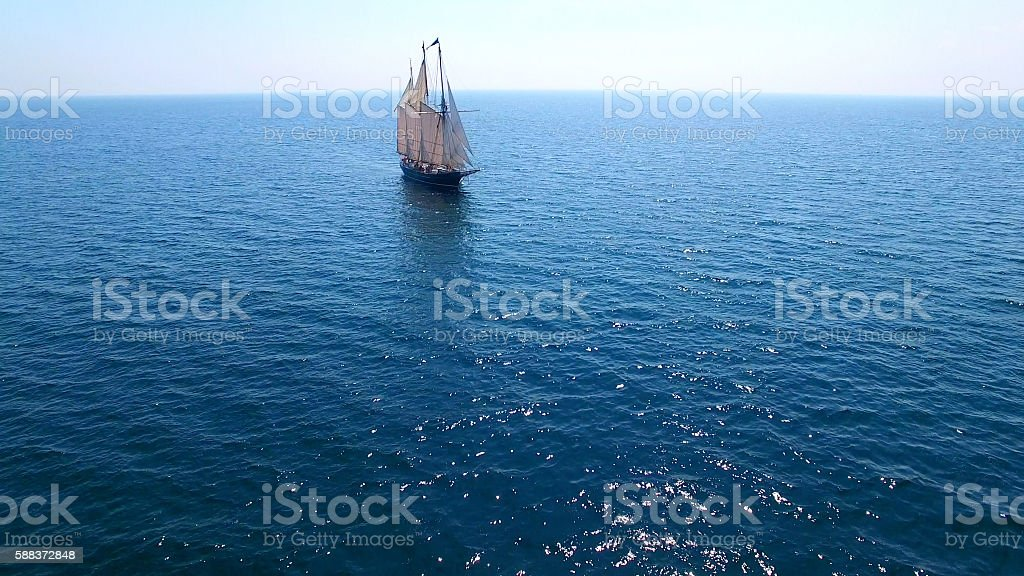 Majestic tall ship alone on a vast blue sea stock photo