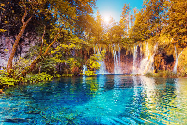 Majestic view on turquoise water and sunny beams.  Location famous resort Plitvice Lakes National Park, Croatia, Europe.