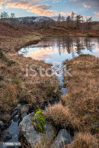 Epic Winter landscape image view from Holme Fell in Lake District towards snow capped mountain ranges in distance in glorious evening light