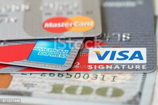 West Palm Beach, USA - September 1, 2016: Closeup detail of the three major credit cards:  VISA, Master Card, and American Express. Credit cards are on a background of a one hundred dollar bill that is only partially visible and in soft focus.