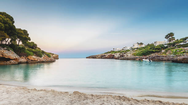 Majorca Beach Sunset Sun sets over beautiful remote beach with white sand. Cala d'or, Mallorca. mediterranean sea stock pictures, royalty-free photos & images