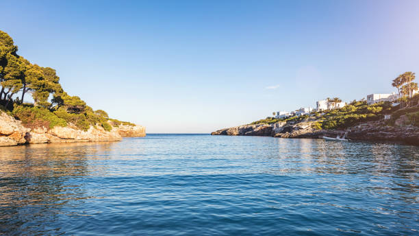 Majorca Sunset over Tranquil Bay Setting sun over beautiful Cala Esmeralda on the island of Majorca, Spain. shallow stock pictures, royalty-free photos & images