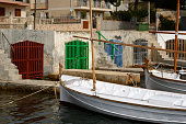 Typical fishing boats moored in natural harbor. Garages for boats in background. Portocolom, Majorca, Spain, Europe.