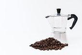 Moka pot and dark roasted coffee bean close up on white background. Vintage espresso coffee maker.