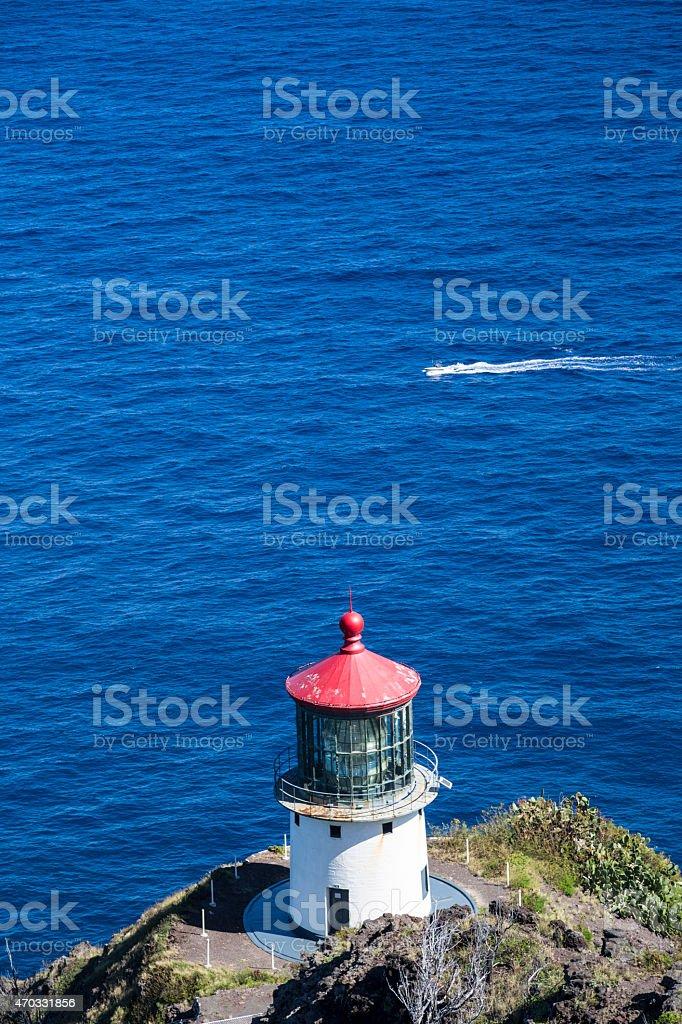 Makapuu Lighthouse on Ohau Island in Hawaii and passing boat stock photo