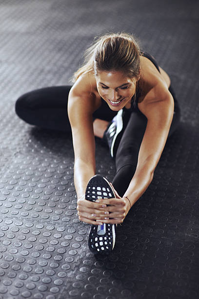 Make a commitment, not an excuse Shot of a young woman stretching her legs before a gym workout touching toes stock pictures, royalty-free photos & images