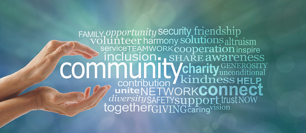 Female cupped hands around the word COMMUNITY and a relevant word tag cloud against a blue green bokeh background