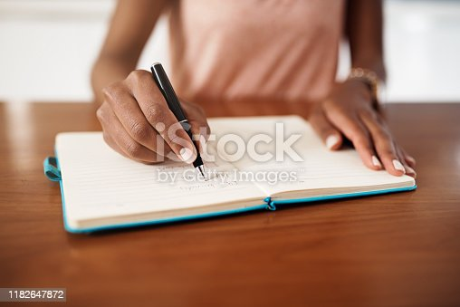 Cropped shot of a woman checking off tasks on a chore list at home
