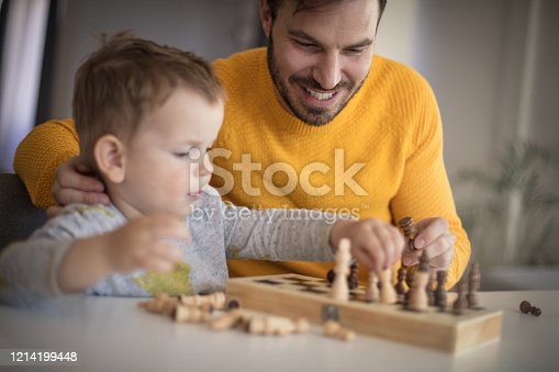 Make a move. Father and son playing chess at home.
