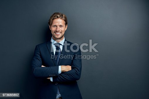 Studio portrait of a handsome young businessman posing against a dark background