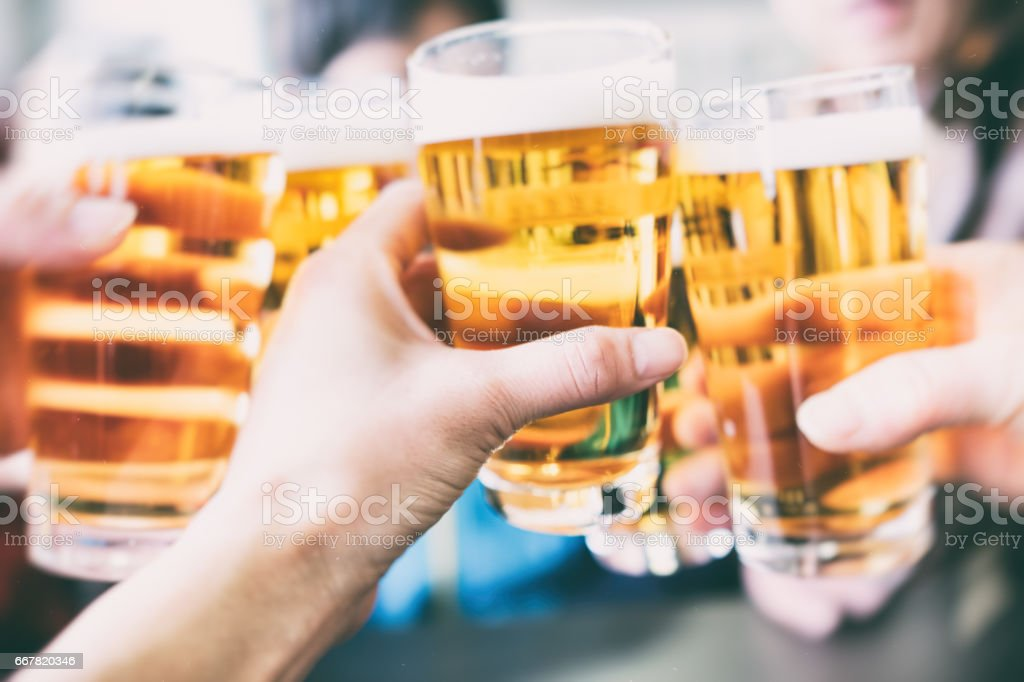 Make a toast with a beer Make a toast with a beer. Asian and Indian Ethnicities Stock Photo