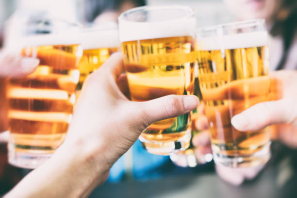 make a toast with a beer - happy hour stock photos and pictures