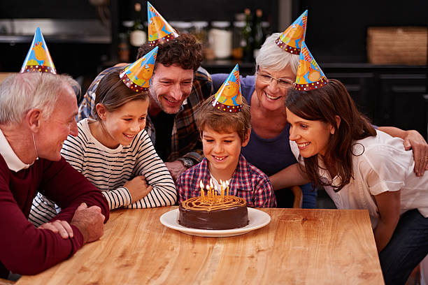 Make a wish before you blow them out Shot of a happy young boy celebrating his birthday with his family birthday wishes for daughter stock pictures, royalty-free photos & images