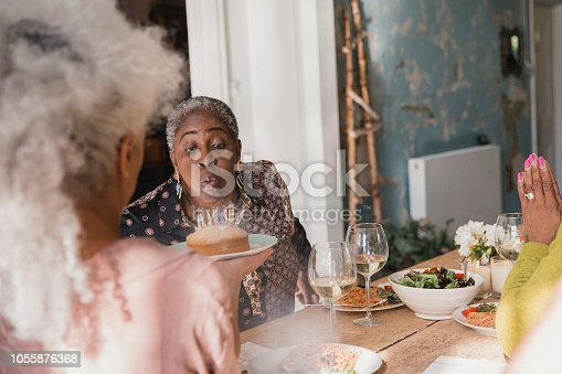 Mature women sitting at a table wishing a happy birthday to their friend as she blows out the candles on a birthday cake.