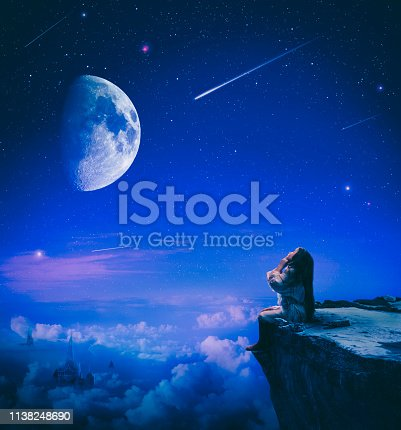 Cute little girl sitting on the cliff up high in the night of falling stars making a wish