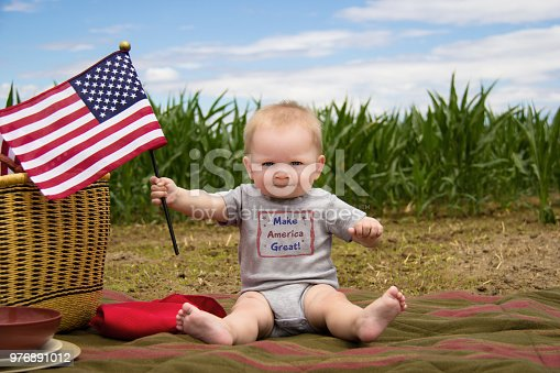 istock Make America Great baby boy with American Flag 976891012