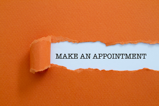 Make an appointment written under torn paper.