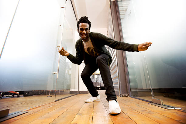 Make dancing toward a camera on the ground A relaxed and fun moment from a confident character creeping up on the low-angle camera in a contemporary creative office environment. snapping stock pictures, royalty-free photos & images