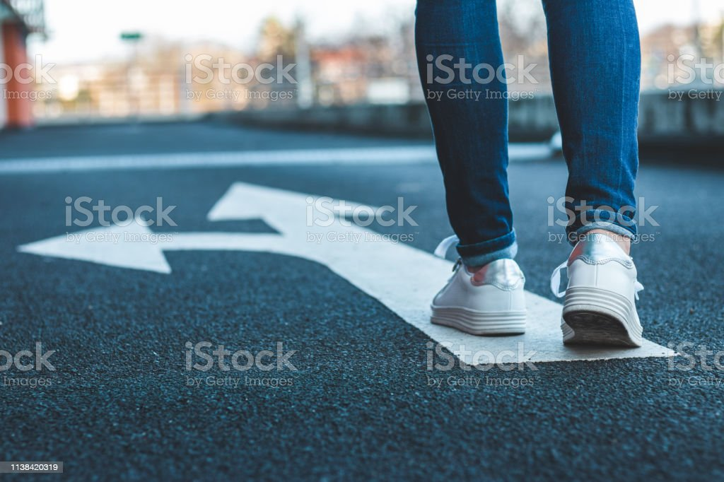 Entscheiden Sie sich, welchen Weg Sie einschlagen wollen. Zu Fuß auf dem Hinweisschild auf Asphaltstraße. - Lizenzfrei Aktivitäten und Sport Stock-Foto