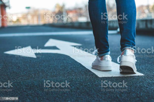 Photo of Make decision which way to go. Walking on directional sign on asphalt road.