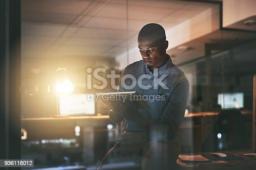 Shot of a young businessman using a digital tablet during a late night in a modern office