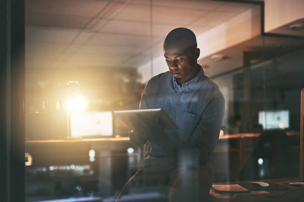 Make every late night count Shot of a young businessman using a digital tablet during a late night in a modern office dedicated stock pictures, royalty-free photos & images