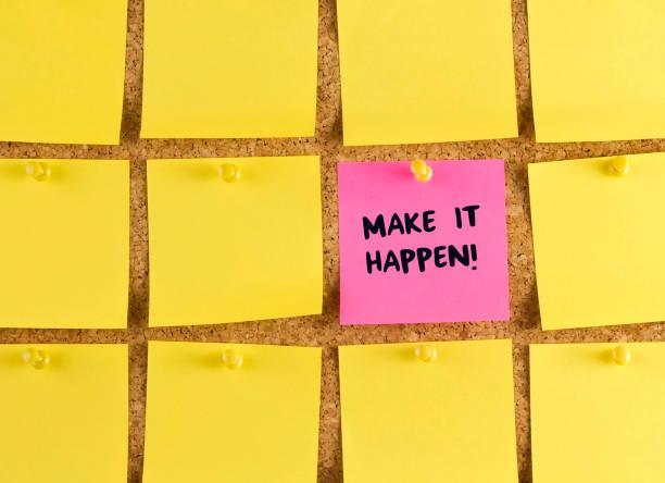 Make It Happen Phrase on Adhesive Note stock photo
