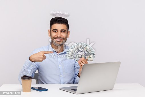 Make money online! Angelic rich businessman with nimbus on head pointing dollar banknotes, encouraging to earn on internet, sitting at laptop workplace. indoor studio shot isolated on white background