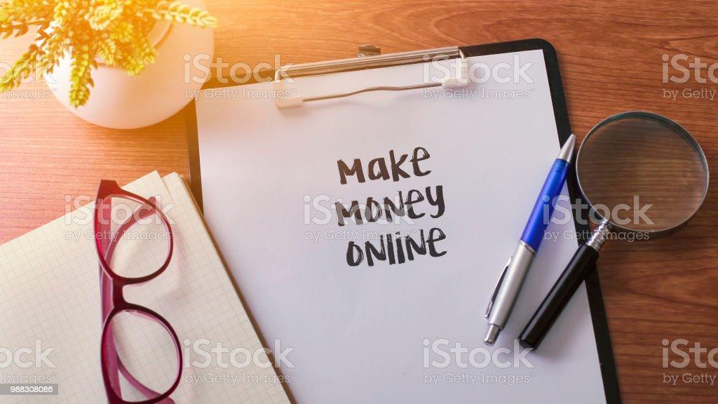 Machen Sie Geld online-Wort auf dem Papier mit Glas Kugelschreiber und grüne Pflanze. – Foto