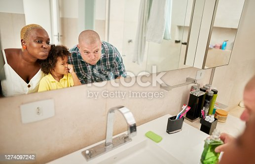 Shot of a funny family looking in the bathroom mirror and doing mouth gargle after tooth brushing