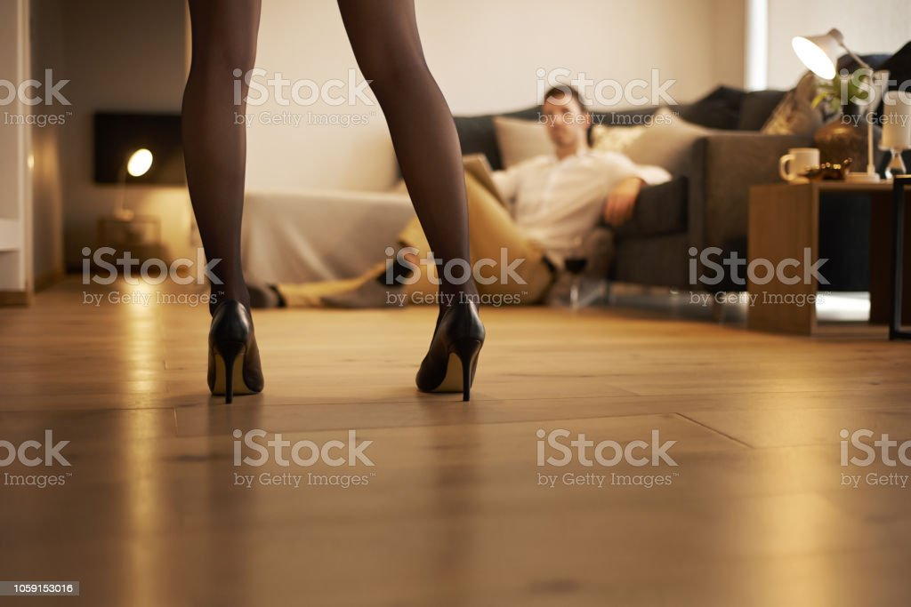 Make room for romance Shot of a sexy young woman seducing her husband at home Adult Stock Photo
