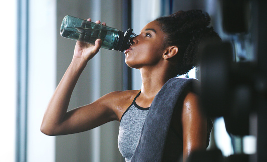 Shot of a sporty young woman drinking water while exercising at the gym