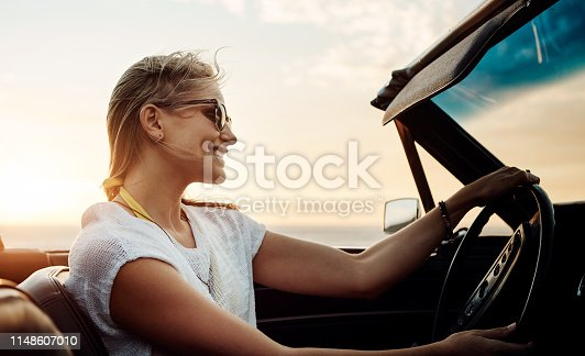Shot of a happy young woman enjoying a summer's road trip