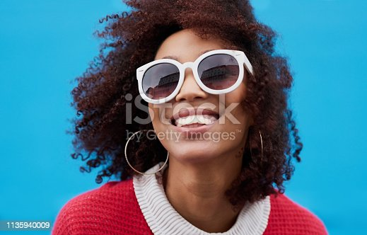 Cropped shot of a young woman wearing sunglasses against a blue background