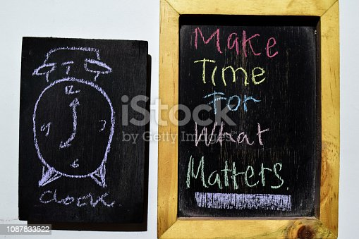 Make Time For What Matters on phrase colorful handwritten on blackboard, alarm clock with white background. Education concept