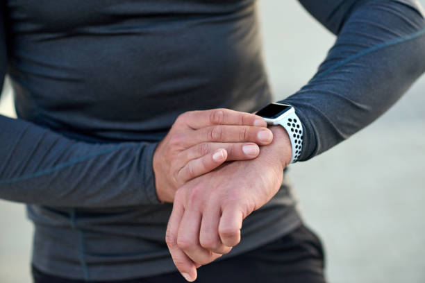 Make time for your health Closeup shot of an unrecognizable man checking his smartwatch while exercising outdoors fitness tracker stock pictures, royalty-free photos & images