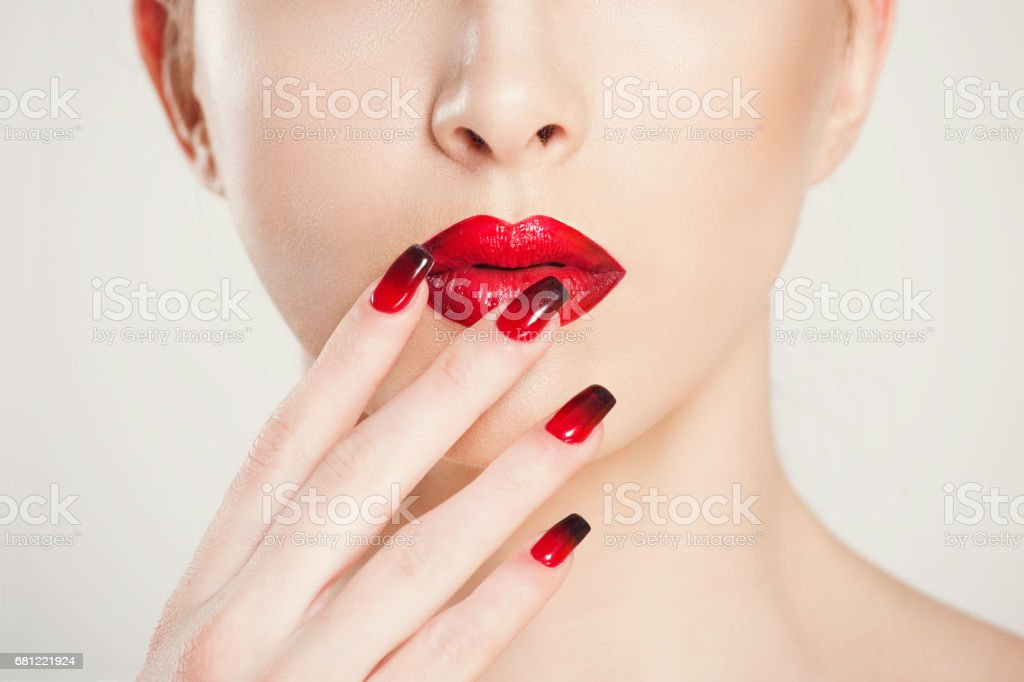 Make up and manicure set. macro cropped image of beautiful gradient of red black manicure and lipstick isolated on white background. stock photo