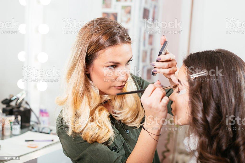 Make up artist applying eye make up on model stock photo