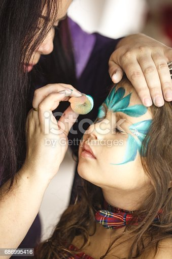 istock Make up artist applying face paint on a little girl 686995416