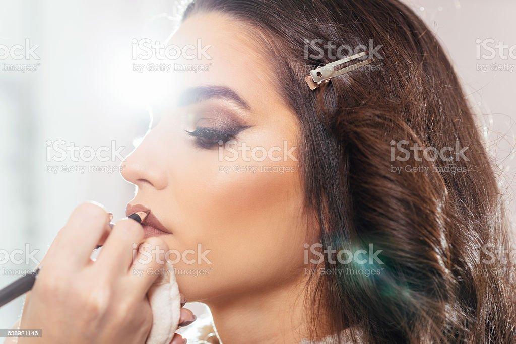 Make up artist applying make up on model stock photo