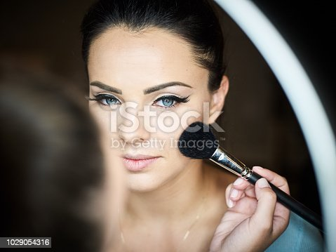 istock Make up artist doing professional make up of young woman. 1029054316