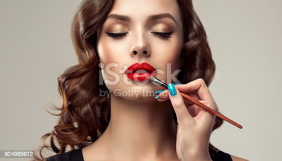 Graceful hands of professional make-up master, with the blue manicure on the nails,  is painting in the red color lips of splendid young woman. Creation of perfect make up in progress. Makeup,manicure and cosmetic.
