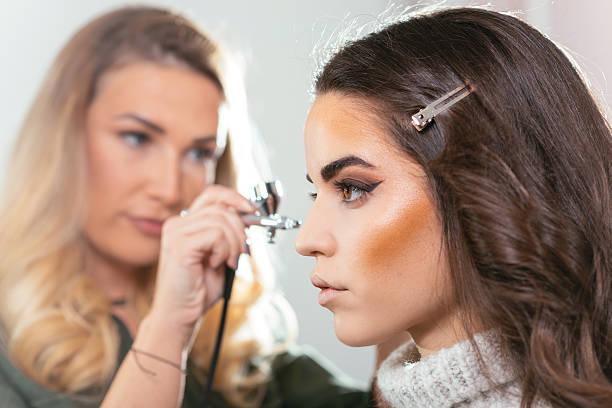 make up artist using airbrush on model - airbrush make up stock-fotos und bilder