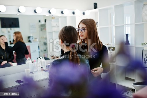 istock Make up artist work in her beauty visage studio salon. Woman applying by professional make up master. Beauty club concept. 935994346